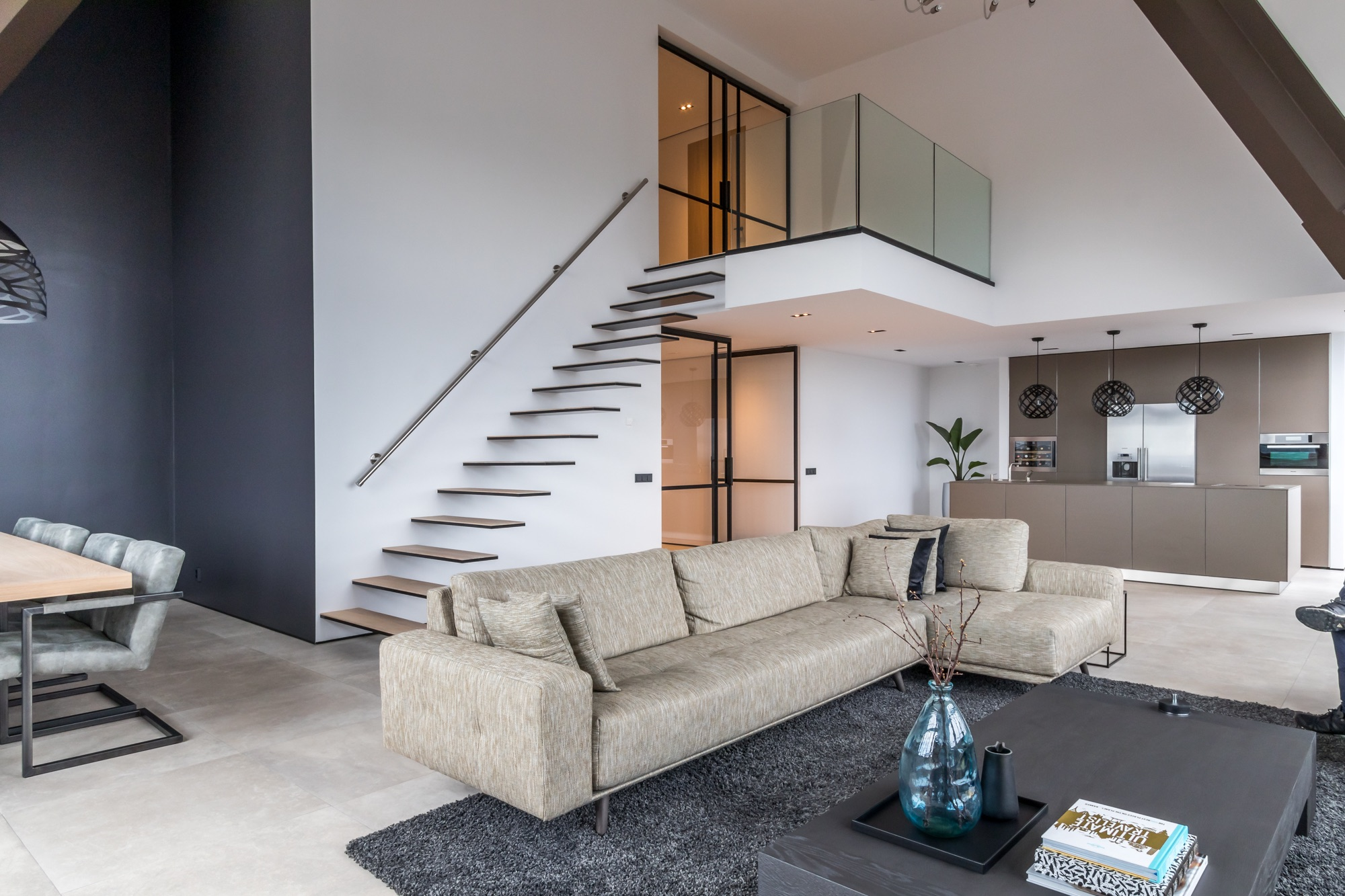 Modern interieur met zwevende stalen trap en glazen balustrade